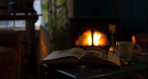 cozy winter scene with fireplace and open book