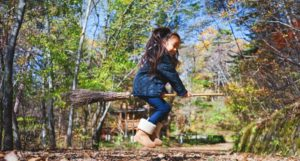 little girl child trying to fly on broomstick outside