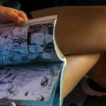 image of a woman sitting and reading a comic book
