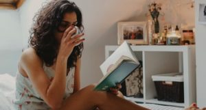 woman drinking tea relaxing and reading in bed