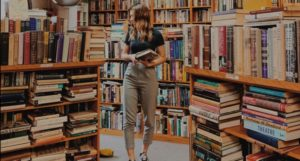 woman holding books in bookstore