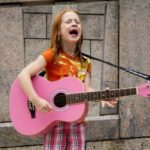 middle grade child singing and playing music on a pink guitar on the street
