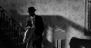 black and white photo of a man in a fedora holding a trench coat at the bottom of a staircase in a wallpapered room