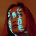 Futuristic image of young Asian woman with orange hair and milky eyes and Chinese writing characters made of light over her face