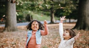 two laughing children tossing dried leaves in the air