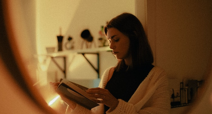 Image of a woman with dark hair reading a book