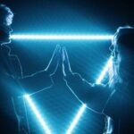 image of teen boy and girl joining hands in front of a blue neon triangle