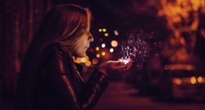 woman blowing sprinkle confetti in the air from cupped hands
