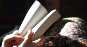 image of hands holding a book while resting on a blanket