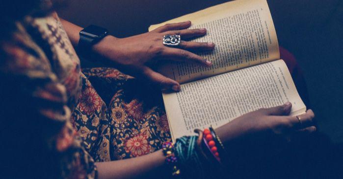 hands holding an open book on a lap https://unsplash.com/photos/uM2D8cPlN_o