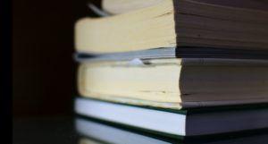 image of a pile of books against a black background https://unsplash.com/photos/fkhesK9SRVU