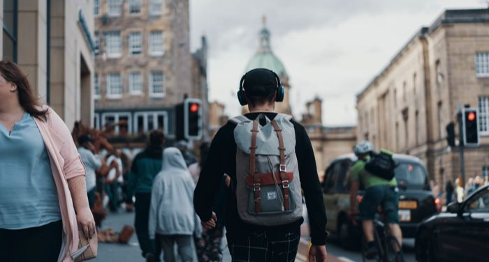 young person wearing a backpack and headphones walking down the street