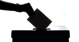 silhouetted image of a hand putting a ballot in a box https://unsplash.com/photos/T9CXBZLUvic