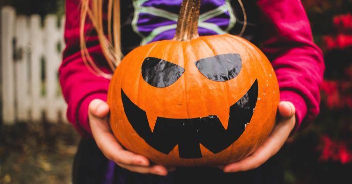 child holding a pumpkin jack o lantern for halloween