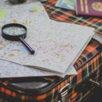 magnifying glass on suitcase and map