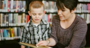 childrens librarian reading aloud in a library with child