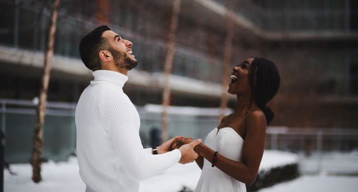 couple standing outside in the snow for winter or holiday romance