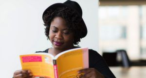 image of a woman reading a yellow book https://unsplash.com/photos/rBYYsIQcPBE