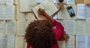 woman writing on top of open books
