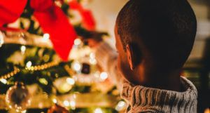 image of a child placing ornament on a christmas tree https://unsplash.com/photos/8uL0fTOBJcQ