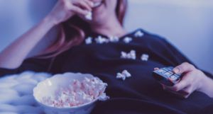 woman watching television and eating popcorn for film and tv