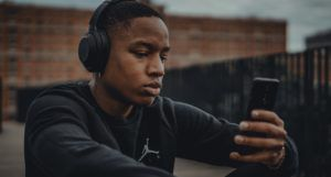 man wearing headphones and looking at cell phone outside