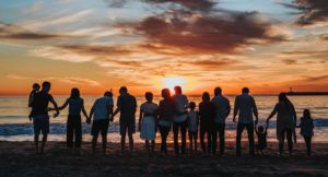 big family gathered on the beach watching the sunset