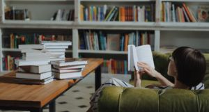 image of a woman reading a book on a green couch and a pile of books on a brown wooden desk https://www.pexels.com/photo/girl-reading-book-on-brown-wooden-table-4861353/