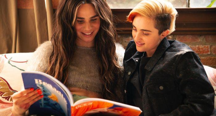 A transfeminine non-binary person and transmasculine gender-nonconforming person reading a magazine together