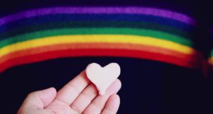 white hand holding a heart under a painted rainbow