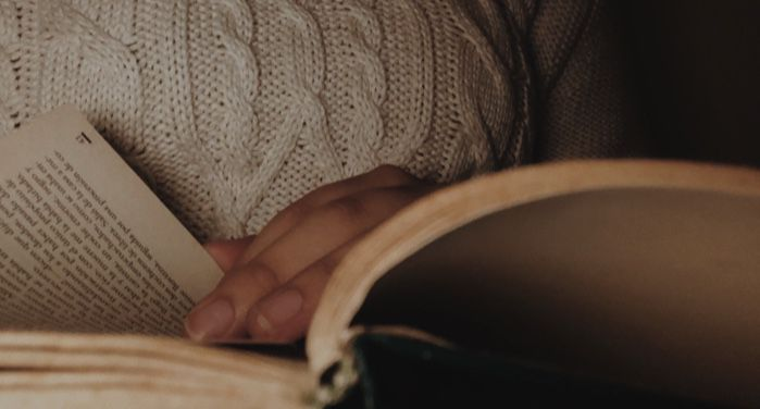 image of a person turning pages of an open book https://unsplash.com/photos/9azhqos3V_o