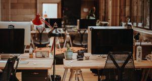several desktop monitors on wooden desks in an office space https://unsplash.com/photos/wgivdx9dBdQ