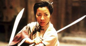 still image of Michelel Yeoh in Crouching Tiger Hidden Dragon; a woman in a defensive stance holding two swords https://www.imdb.com/title/tt0190332/mediaviewer/rm2623090432/