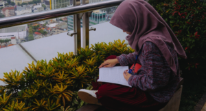 indonesan woman in hijab reading a book