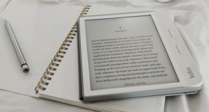 Kobo ereader on top of journal with stylus for reading ebooks feature