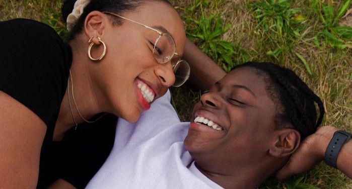 two Black women embracing while lying in grass https://unsplash.com/photos/MQjzK560aCQ