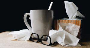 kleenex glasses and mug of tea for sick day