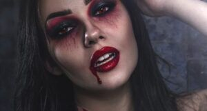 image of a woman with red and black smokey eye makeup, red lipstick, and makeup that looks like blood dripping from her mouth https://unsplash.com/photos/HWUiNmpeHbg