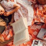 mother or parent reading to child or daughter on a picnic blanket