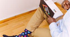 photo credit: Adeolu Eletu. a partial view of a Black person sitting with one leg propped up on the other, reading a book. they are wearing khaki pants and you can see a brightly colored polka dot sock.