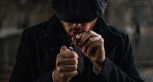 image of a man in a black knit cap lighting a cigarette https://unsplash.com/photos/VP_4ijGm0n0
