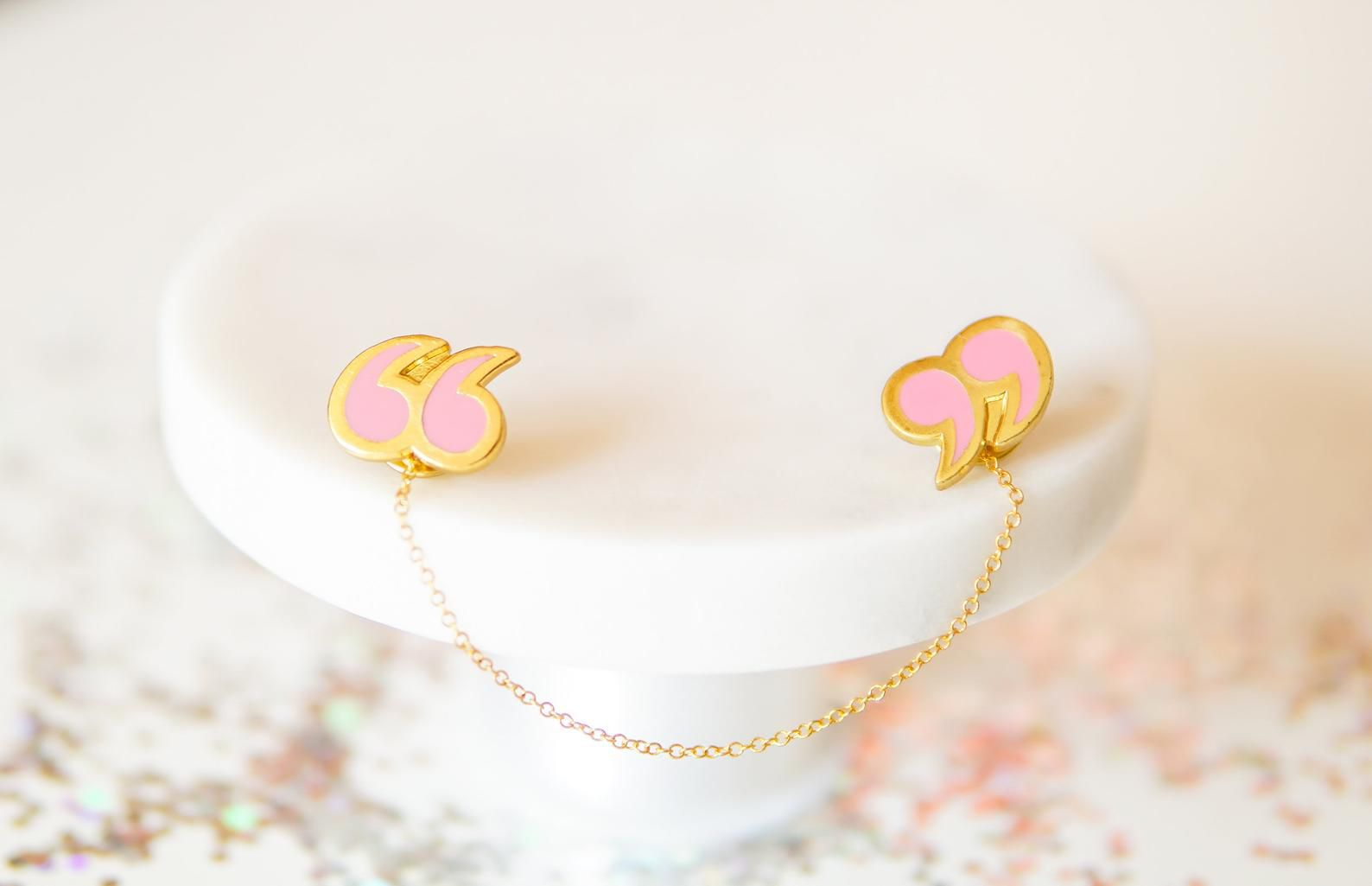 Two pink and gold quotation mark pins, linked by a gold chain. They are resting on a white stand.
