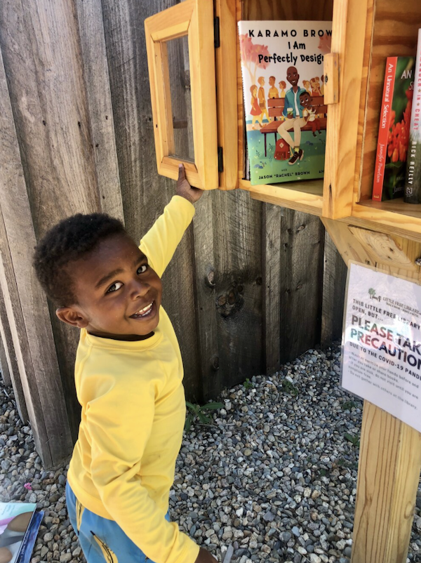 Image of a young Black boy opening a little free library. Image used with permission from Sarah Kamya, founder of Little Free Diverse Libraries