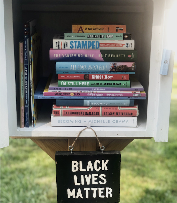 """Image of a Little Free Library with a stack of diverse books and a sign reading """"Black Lives Matter."""" Image used with permission from Sarah Kamya, founder of Little Free Diverse Libraries."""