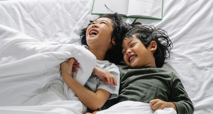 kids laughing in bed with book behind them