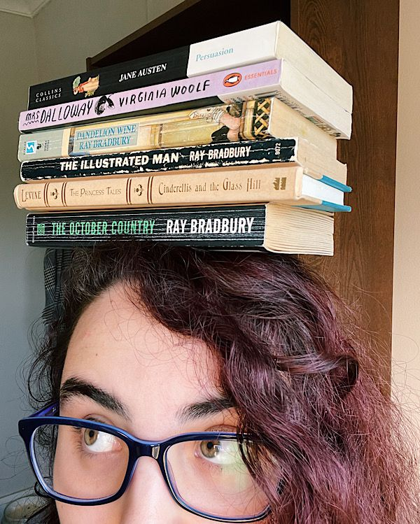 Up-close of a woman wearing glasses, with books stacked on her head