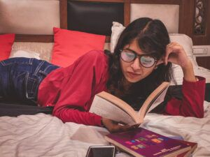a woman reading a book in bed