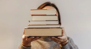 person obscuring their face with a stack of books https://www.pexels.com/photo/faceless-student-with-pile-of-books-on-light-background-5984619/