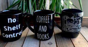 Image of three black coffee mugs with book themes