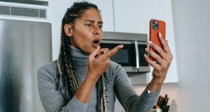 Black woman pointing at phone